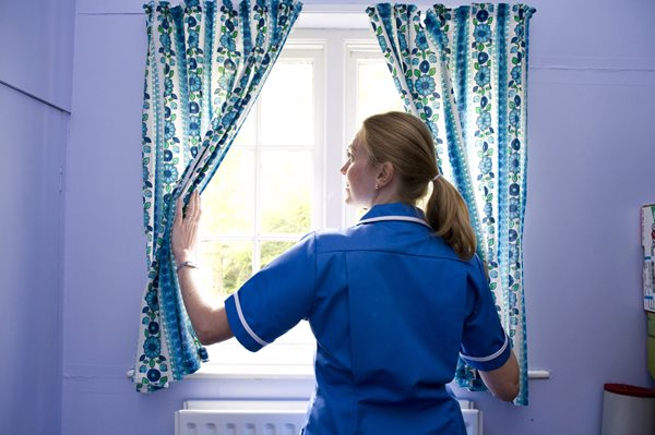 End of life, carer closing a curtain