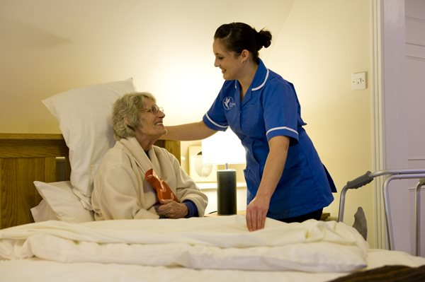 Live-in care, carer helping person in bed