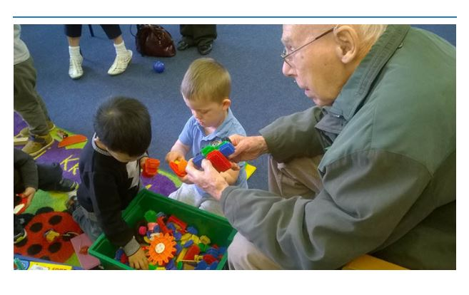 Bluebird Care customer playing with children from Exeter Road Primary school