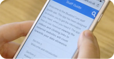 A close up of a white iPhone being held in someone's hands with the Staff Guide app open.