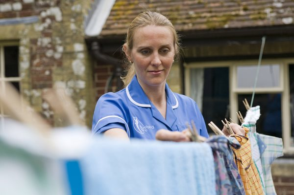 End of life care, carer hanging washing out